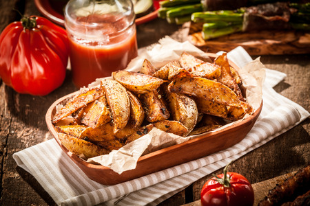 accompagnement: Delicious vegetarian cuisine with a platter of spicy potato wedges served with fresh tomato juice for a tasty snack or accompaniment to a summer picnic