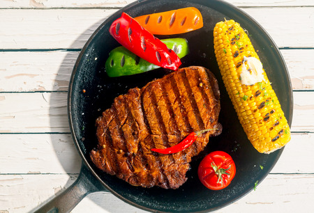 Barbecued rib eye beef steak with grilled corn on the cob, colorful peppers and a tomato, served on a skillet on a white wooden table outdoors in sunshine, overhead view 写真素材