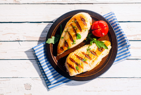 chicken breast: Two delicious fresh grilled chicken breasts seasoned with herbs served on a plate with tomato on a white wood table, overhead view in summer sunshine