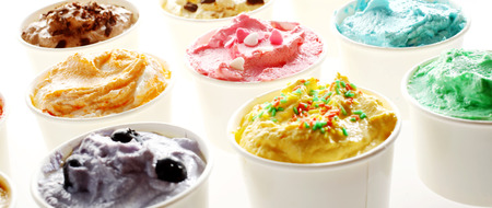 flavours: Delicious tubs of creamy summer ice cream in assorted flavours viewed low angle with blueberry, caramel and mint in the foreground over a white background