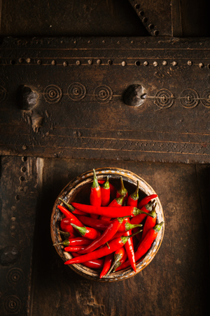 flavoring: Bowl of spicy pungent red hot cayenne chili peppers for flavoring cooking viewed from overhead on an old rustic wooden table with copyspace