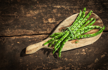 over the counter: Healthy grilled green runner beans cooked over a summer BBQ served on a rustic wooden board on an old table or counter, view from above with copyspace