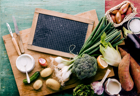 shabby chic background: Healthy farm fresh vegetables with broccoli, onions, potato, sweet potato, shallots, garlic and kohlrabi for preparing a vegetarian or vegan dinner around a blank slate on a shabby chic background