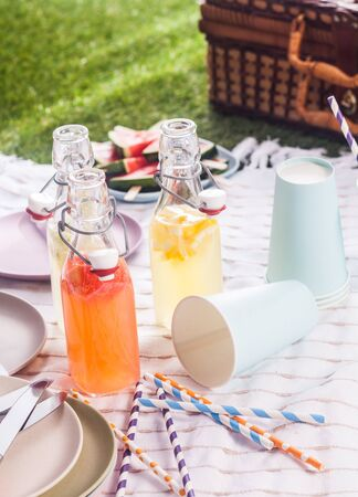 pic nic: Fresh homemade fruit juice blend served in glass bottles for a country picnic in the summer sun with disposable cups, plates and a picnic hamper on the grass