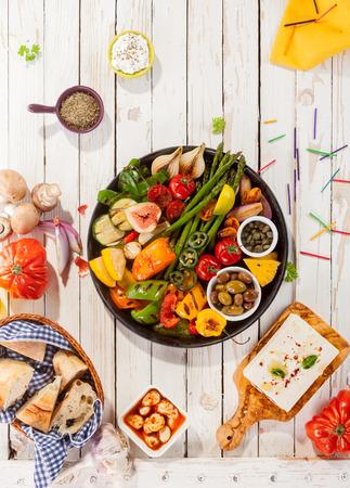 Hög vinkel tanke på färgglada grillade grönsaker diskens white Picnic Table omgiven av färskt bröd och ost på Outdoor Party
