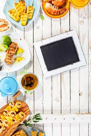 top down: Small Chalkboard on Rustic White Wooden Table Surrounded by Grilled Seafood and Fruit Dishes with Copy Space