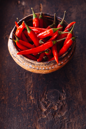 cayenne: High Angle View of Bright Red Chili Peppers in Rustic Bowl on Wooden Surface with Copy Space