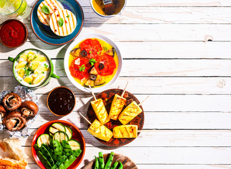 High Angle View of Vegetarian Mediterranean Meal of Grilled Fruit and Vegetables Spread Out on White Wooden Picnic Table with Copy Space Stockfoto