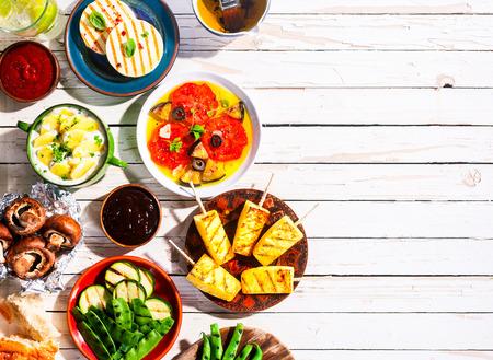 luz do sol: Vista de Cima de Vegetariana Mediterrâneo refeição de grelhados Frutas e Legumes espalhados em branco da tabela de piquenique de madeira com espaço da cópia