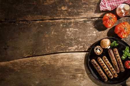 frankfurters: Grilled barbecued sausage with portobello mushrooms and fresh tomato on an old rustic wooden with cracks viewed from above, copyspace Stock Photo
