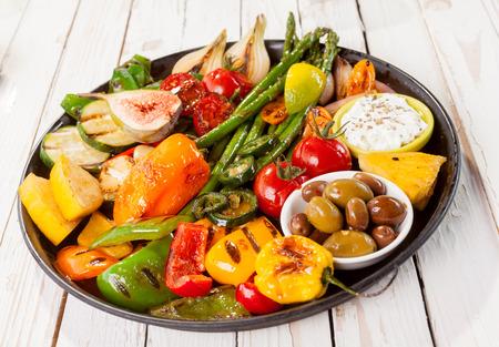 bounty: Hasta cerca de colorido Bounty vegetales a la parrilla en sartén de hierro fundido con aceitunas y Dip Descansando en blanco pintado Mesa de picnic de madera