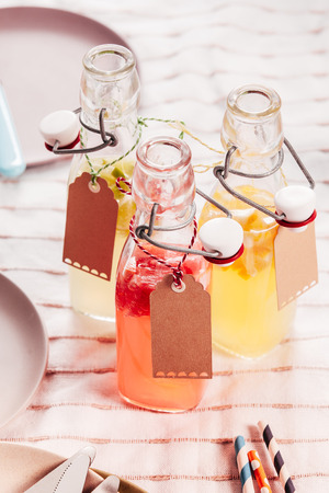 pic nic: Glass bottles of healthy homemade fresh fruit juice with blank tags with copyspace served outdoors in the sunshine for a summer picnic Stock Photo