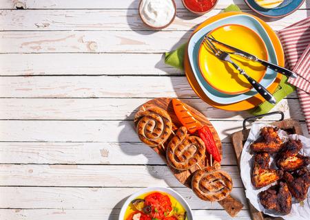 almuerzo: Vista de �ngulo alto de la parrilla Salchichas y alas de pollo en Mesa de picnic con placas de colores y Cubiertos, Espacio en blanco en la tabla con comida de Barbequed