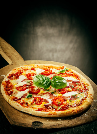 Close Up of Fresh Baked Pizza Topped with Tomatoes, Basil and Cheeses Served on Wooden Pizza Paddle with Dark Grey Background with Copy Space