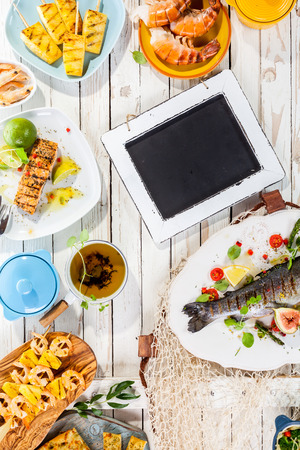 langoustine: Small Chalkboard on Rustic White Wooden Table Surrounded by Grilled Seafood and Fruit Dishes