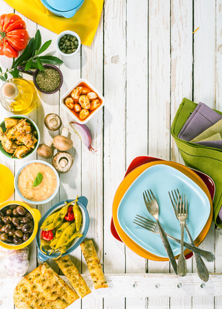 mediterranean food: High Angle View of Mediterranean Appetizers and Colorful Plates Arranged on Rustic White Wooden Picnic Table with Copy Space