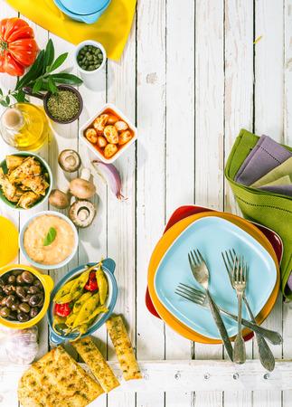 Hoog standpunt van de mediterrane hapjes en kleurrijke platen Gerangschikt op Rustieke Witte Houten Picknick met kopiëren ruimte Stockfoto