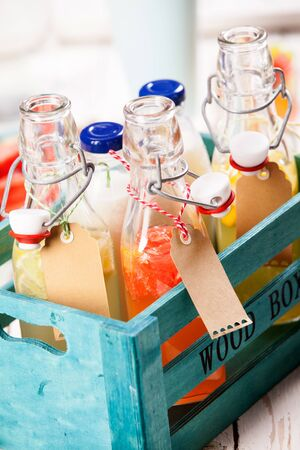 pic nic: Assorted fresh tropical fruit juice and milk served in clear glass bottles with blank labels in a rustic blue wooden crate outdoors at a summer picnic Stock Photo