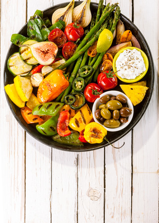 top down: High Angle View of Colorful Grilled Vegetable Bounty on Cast Iron Pan with Olives and Dip Resting on White Painted Wooden Picnic Table with Copy Space Stock Photo