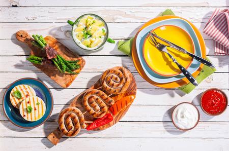 Hoog standpunt van Barbequed Maaltijd van gegrilde worstjes en Prepared bijgerechten gerangschikt op wit Picknick