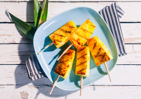 pineapple: High Angle View of Grilled Skewers of Fresh Pineapple Wedges on Blue Plate on White Wooden Table with Striped Napkin