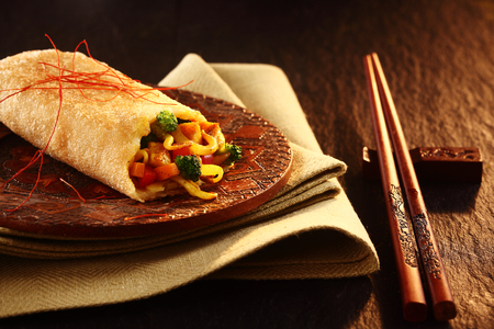 chop sticks: Close Up of Decorative Chop Sticks and Spring Roll on Textured Wooden Table Surface in Warm Mood Lighting Stock Photo