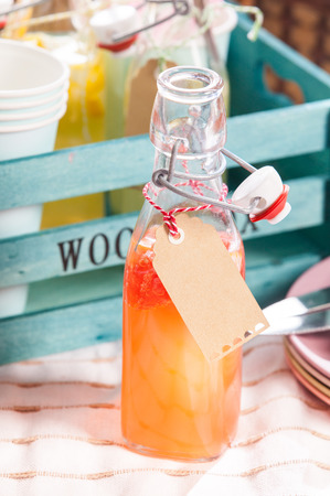 pic nic: Freshly liquidized homemade fruit juice served in a glass bottle with a blank tag around the neck for a summer picnic outdoors