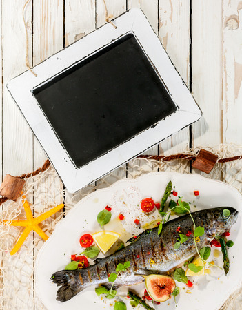trout: High Angle View of Blank Chalkboard on Rustic White Table with Whole Garnished Grilled Fresh Fish on White Platter with Fishing Net