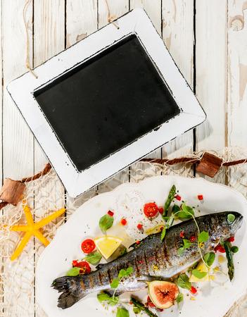 trucha: Opinión de alto ángulo de la pizarra en blanco en la rústica mesa blanca con Whole adornado parrilla pescado fresco en plato blanco con red de pesca