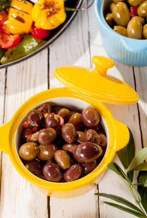 high angle: High Angle View of Bright Yellow Bowl of Olives with Lid on Wooden Table Surrounded by Grilled Vegetables and Antipasti Stock Photo