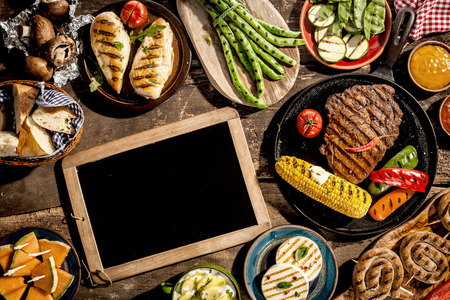 High Angle View of Blank Chalkboard Amongst Grilled Meal of Steak, Chicken and Vegetables Spread Out on Rustic Wooden Table at Barbeque Party