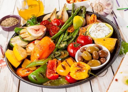 bounty: Close Up of Colorful Grilled Vegetable Bounty Tray on Cast Iron Pan with Olives and Dip Resting on White Painted Wooden Picnic Table