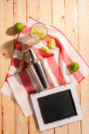 blank slate: Cocktail shaker and an iced tropical cocktail with lime and lemon on a striped bar cloth on a wooden table, overhead view with a blank slate for your beverage recipe Stock Photo