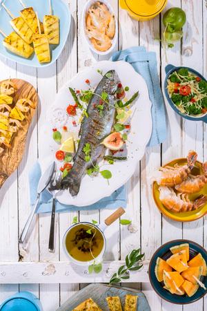 飾ると他のシーフード料理と素朴な白い木製テーブル表面の調味料の白い大皿にまるごと焼き魚のハイアングル