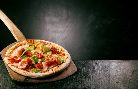 Ham, tomato and arugula, or rocket, pizza served at a pizzeria or restaurant on a long handled wooden board on a rustic counter with copyspace behind