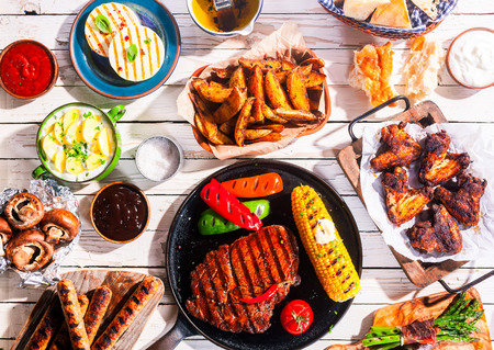 chorizos asados: Opinión de alto ángulo de comidas a la plancha - apetitosos Barbequed Carnes y verduras dispuestas en blanco Mesa de picnic de madera Foto de archivo