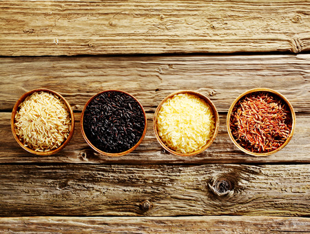 Four different varieties of dried rice, wild, basmati, long-grain and red, displayed in individual wooden bowls in a line on an old rustic weathered wooden table, overhead view with copyspace Фото со стока - 41699182