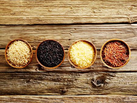 Vier verschillende soorten gedroogde rijst, wild, basmati, langkorrelig en rood, weergegeven in individuele houten kommen in een rij op een oude, rustieke, verweerde houten tafel, bovenaanzicht met copyspace