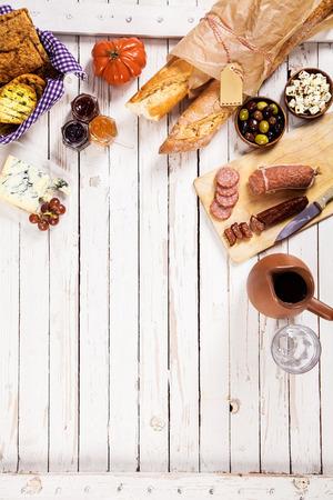 queso blanco: Baguettes recién horneados, vino tinto, queso y chorizo ??servido para un picnic de verano al aire libre en una mesa de madera blanco con copyspace, vista aérea Foto de archivo