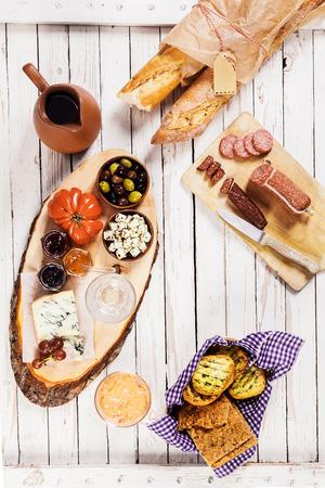 スパイシーなソーセージ、チーズにトマトとオリーブと新鮮なバゲットを添えて赤ワイン屋外夏おやつの白い木製ピクニック テーブルの上の陶器の