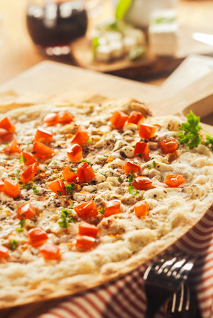 pizza base: Tasty Elsass Alsace pizza on a thin crispy base flame grilled in a pizzeria and topped with mozzarella cheese, herbs, onions and ham served on a wooden board Stock Photo