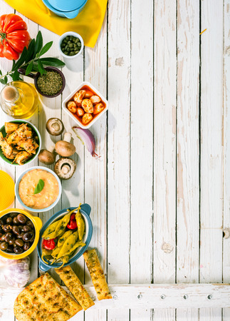 picnic: High Angle View of Mediterranean Appetizers Spread Out on Rustic White Wooden Picnic Table with Copy Space