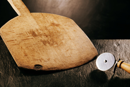 Wooden Pizza Paddle Board and Circular Pizza Cutter, Tools of the Trade on Dark Textured Counter Surface