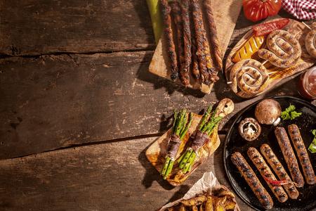 embutidos: Comida a la parrilla Surtido incluyendo salchichas, trozos de papa y envolturas tocino espárragos de una barbacoa de verano en una mesa de picnic de madera rústica con copyspace