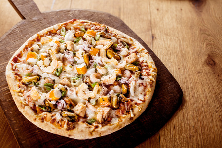 fish shop: High Angle View of Fresh Baked Seafood Pizza Topped with Fresh Ingredients Served on Wooden Cutting Board on Table