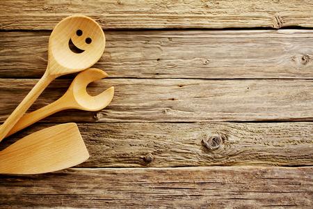 大まかな素朴な質感を持つ高齢者の風化ヴィンテージ木の背景と copyspace たっぷりの木製の調理器具国境