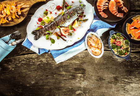 Whole Grilled Fish on White Platter Surrounded by Seafood Dishes on Rustic Wooden Table with Linen Napkins and Cutlery with Copy Space Stockfoto