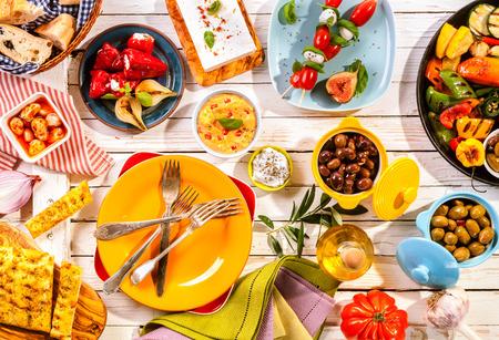 Hög vinkel tanke på Beredda färgglada Medelhavet måltid utspridda på vitmålad trä picknickbord med ljusa tallrikar och bestick Stockfoto