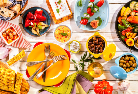High Angle View of Prepared Colorful Mediterranean Meal Spread Out on Painted White Wooden Picnic Table with Bright Plates and Cutlery Archivio Fotografico
