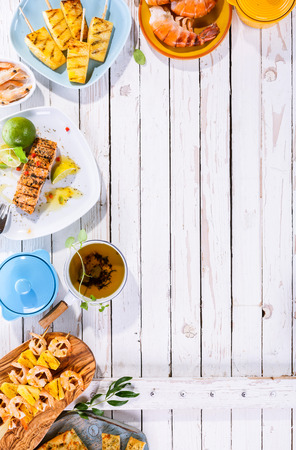gamba: Platos alto ángulo de vista de la parrilla de la fruta y Marisco dispersos en blanco Tabla superficie de madera con espacio de copia
